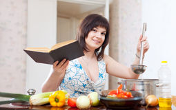 Housewife cooking with cookery book Stock Photography