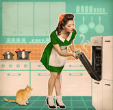 Young housewife cooking in an oven.Retro kitchen room interior Royalty Free Stock Image