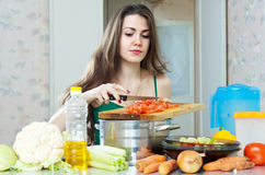 Young housewife cooking with vegetables Stock Photos