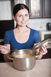 Young housewife cooks food in kitchen Royalty Free Stock Photography