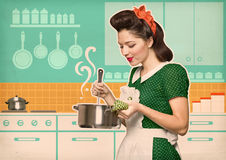 Young housewife cooks in the kitchen Royalty Free Stock Photos