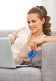 Young housewife with credit card using laptop Stock Photo