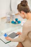 Young housewife with credit card using tablet pc . rear view Stock Photo
