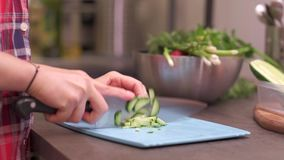 Young housewife cuts cucumber on plastic board. Young woman housewife cuts cucumber on a blue plastic cutting board. Preparing food ingredients on a stone stock footage