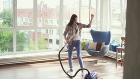 Young housewife dancing and vacuuming. At home stock video footage