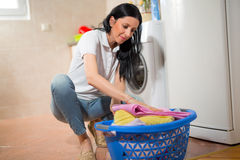 Young housewife is doing laundry with washing machine Stock Photos