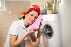 Young housewife is doing laundry with washing machine Royalty Free Stock Photography