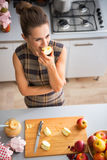 Young housewife eating apple in kitchen Royalty Free Stock Photo