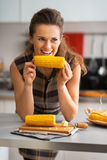 Young housewife eating boiled corn in kitchen Stock Image