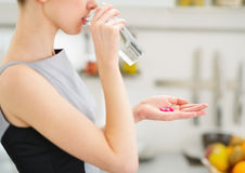 Young housewife eating pills and drinking water. Closeup on young housewife eating pills and drinking water Royalty Free Stock Image