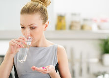 Young housewife eating pills and drinking water Stock Image