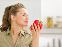 Young housewife enjoying fresh red bell pepper Royalty Free Stock Images