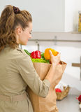 Young housewife examines purchases after shopping. In kitchen. rear view stock image