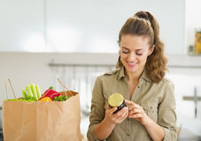 Young housewife exploring purchasings after shopping in kitchen Stock Images