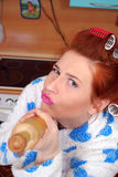 The young housewife in hair curlers threatens having aimed a rolling pin. Discontent, emotions Royalty Free Stock Photography