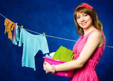 Young housewife hanging clothes on clothesline Royalty Free Stock Images
