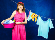 Young housewife hanging clothes on clothesline Stock Photos