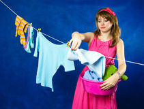 Young housewife hanging clothes on clothesline Stock Images