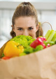 Young housewife hiding behind shopping bag full of vegetables Stock Image