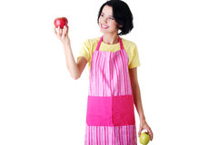 Young housewife holding apple, in kitchen apron. Royalty Free Stock Images