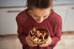 Young housewife holding plate with mushrooms Royalty Free Stock Photography