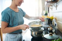 Spaghetti in colander. Young housewife with hot cooked spaghetti in colander standing by electric stove in the kitchen royalty free stock photography