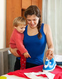 Young housewife  ironing at ironing board Stock Photography