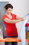 Young housewife ironing shirt Royalty Free Stock Images
