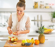 Young housewife making fruit salad in kitchen Royalty Free Stock Photography