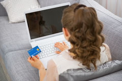 Young housewife making online shopping. rear view Stock Image