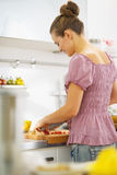 Young housewife making salad in kitchen . rear view Royalty Free Stock Images