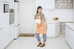 Young housewife mixing dough in the kitchen royalty free stock photos