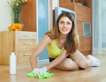 Young housewife polishing parquet floor. With furniture polish at home stock image