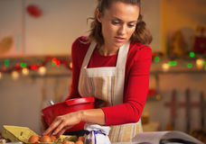 Young housewife preparing christmas dinner in kitchen. Young housewife in red dress preparing christmas dinner in kitchen Stock Images