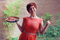 Young housewife presenting figs tart. Young smiling woman holding tart in the garden Royalty Free Stock Photography