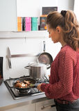 Young housewife putting pan on stove Royalty Free Stock Photography