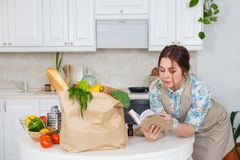 Young housewife with recipes book. In the kitchen Royalty Free Stock Photos