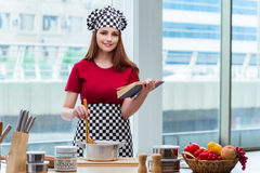 The young housewife referring to recipe book Royalty Free Stock Images
