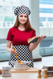 The young housewife referring to recipe book Stock Photo