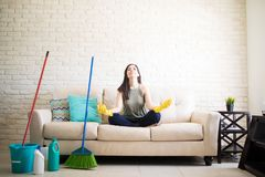 Woman meditating after cleaning house. Young housewife relieving stress by meditating sitting on sofa wearing yellow rubber gloves and cleaning equipments kept Royalty Free Stock Photos