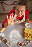 Young housewife showing hand smeared in flour Stock Photo