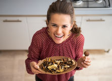 Young housewife showing mushrooms Royalty Free Stock Photo
