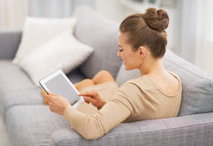 Young housewife sitting on couch using tablet pc . rear view Stock Image