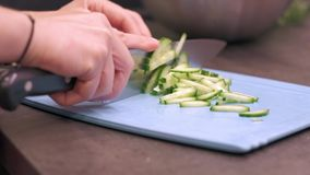 Young housewife slices cucumbers on plastic board. Young woman housewife slices cucumbers on a blue plastic cutting board. Preparing food ingredients on a stone stock video footage