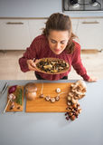 Young housewife smelling dried mushrooms Stock Photography