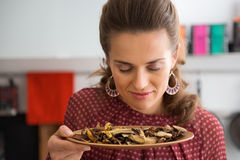 Young housewife smelling dried mushrooms Royalty Free Stock Photography