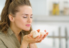 Young housewife smelling mushroom in kitchen Royalty Free Stock Photography
