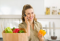 Young housewife sort purchases after shopping. And talking mobile phone royalty free stock image