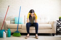 Beautiful woman sitting on couch holding head with cleaning equi. Young housewife suffering from headache after cleaning living room Royalty Free Stock Photo