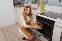 Young housewife taking cupcakes from oven Royalty Free Stock Photography